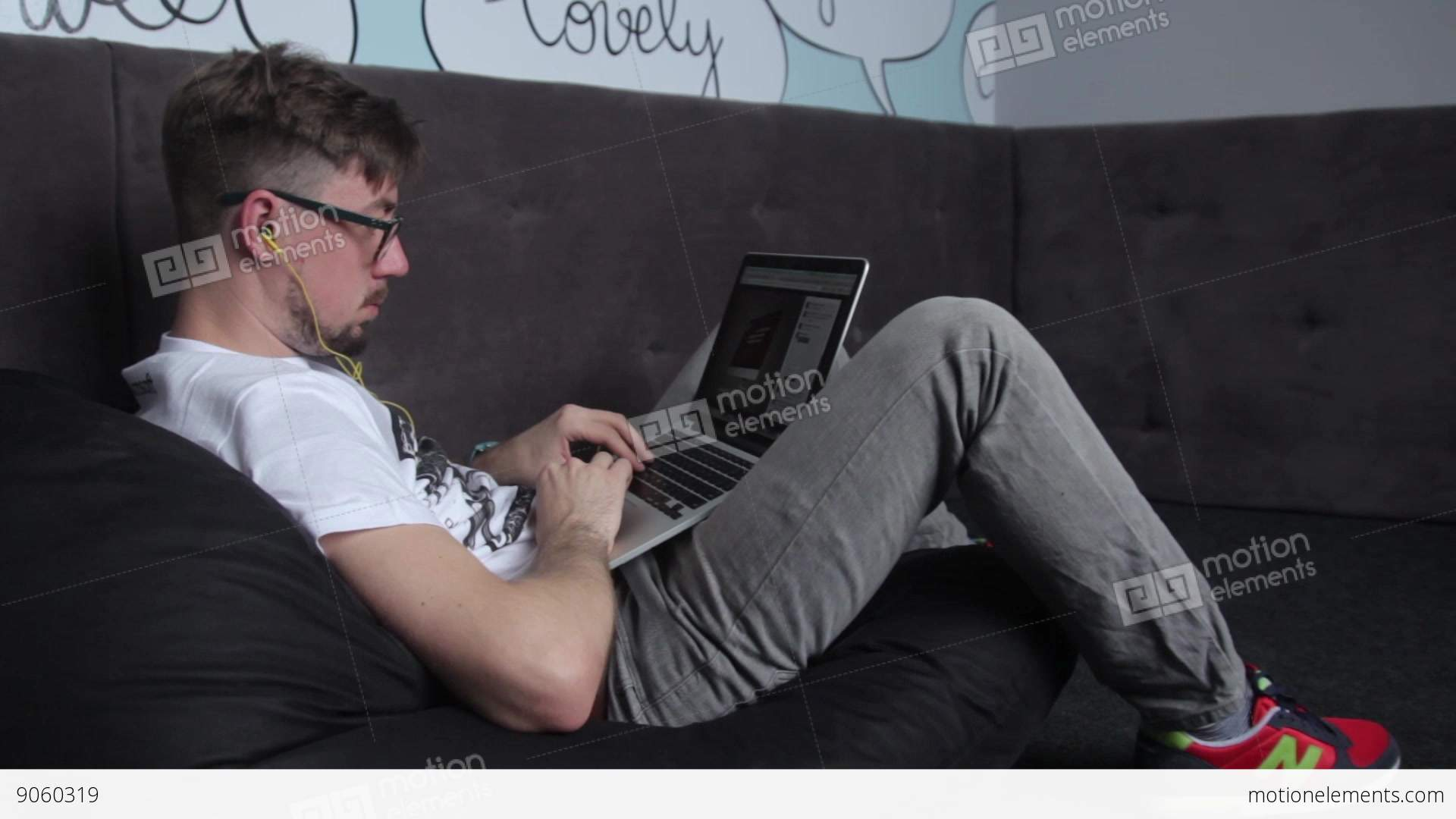 The Guy Working With Laptop Laying On The Couch Stock video ...