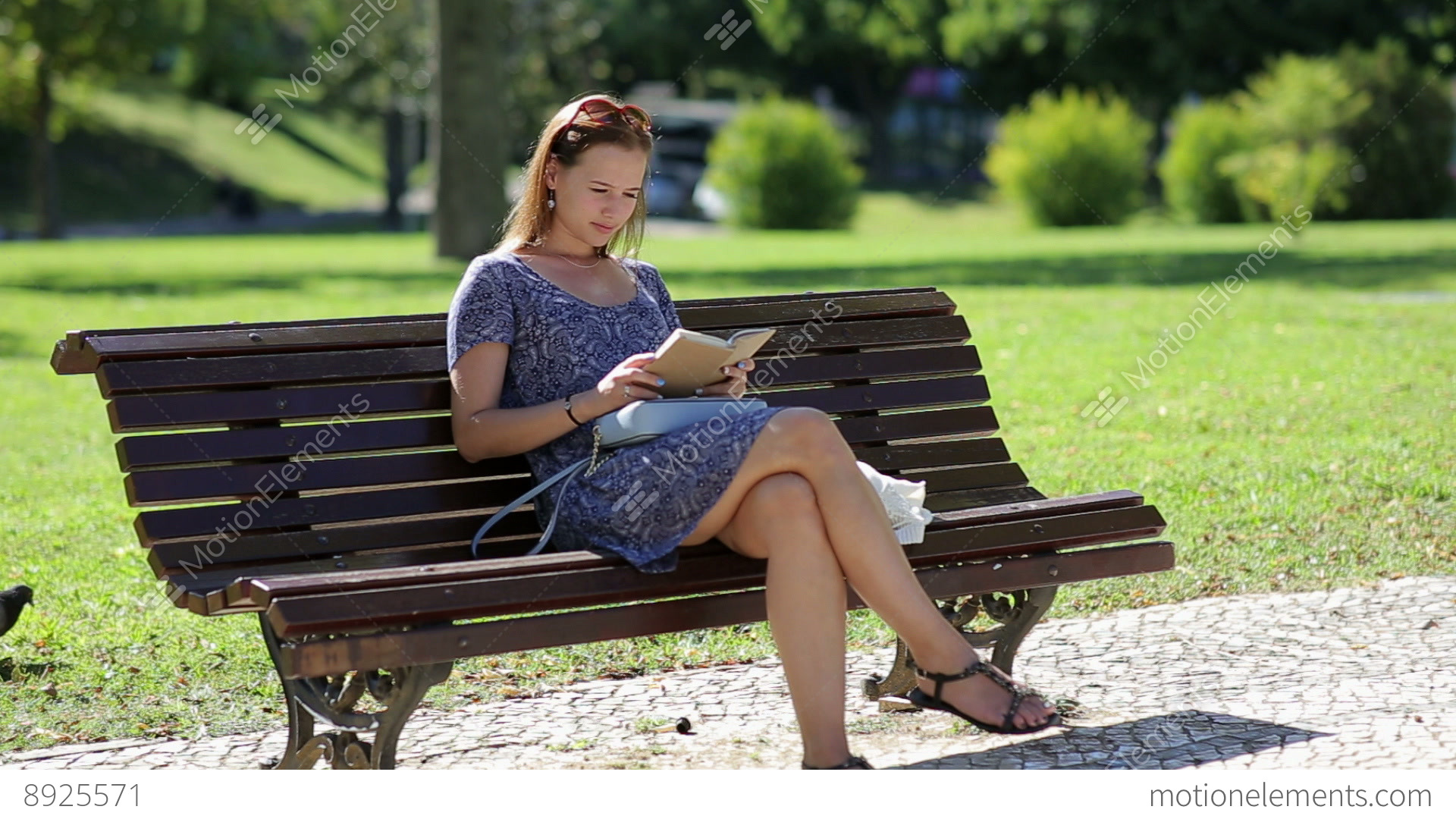 Young Woman Reading A Book And Sitting On A Bench Outside In A Park In Summer B Stock Video