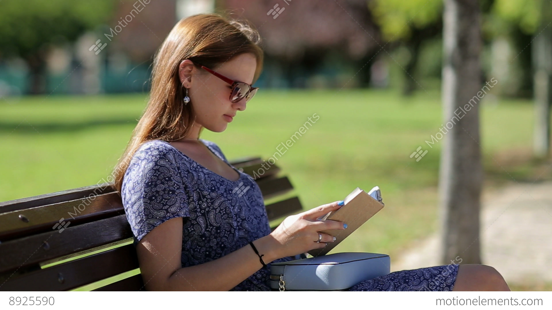 young woman reading a book and sitting on a bench outside in a park