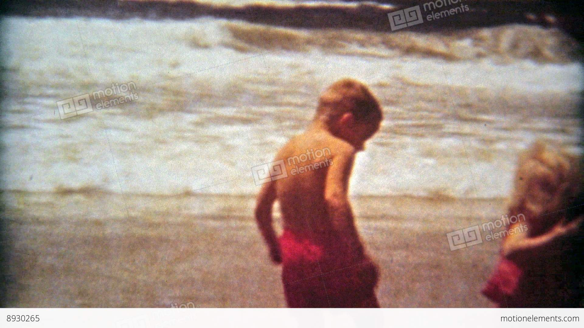 1961: Kids 1st Time At Beach Boy Scared Of Ocean Waves Stock video footage