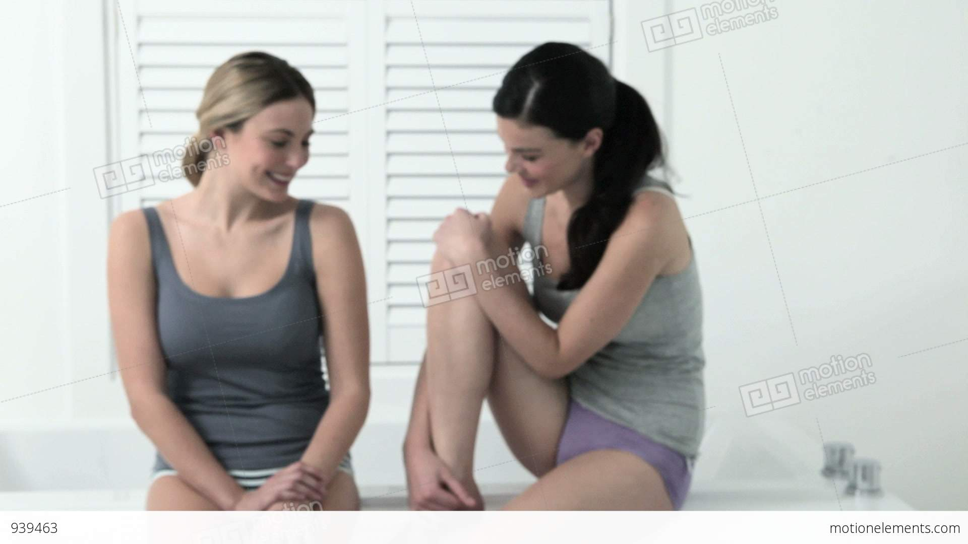 Two young woman sitting on edge of bathtub stock video for Sit in tub shower