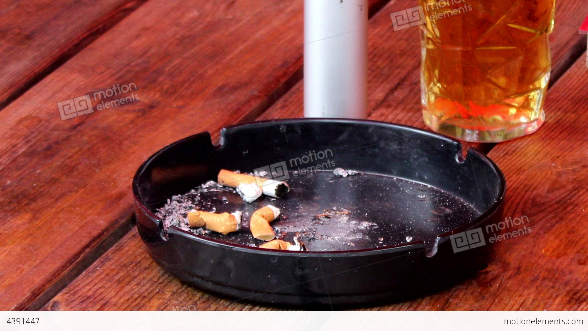 ashtray with cigarette butts and a pint of beer stock video footage