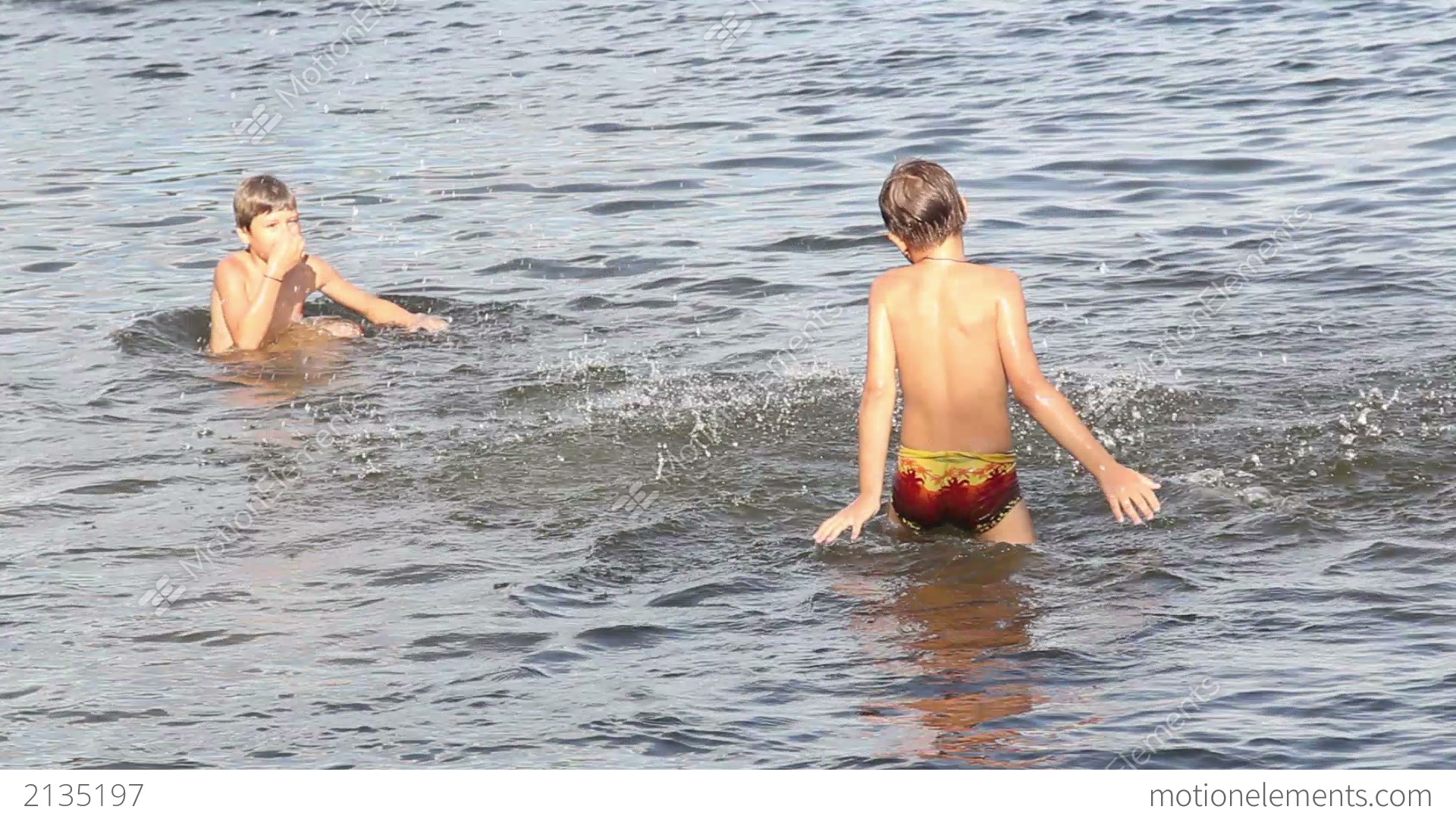 Young boys swim into the Yamuna river looking for coins