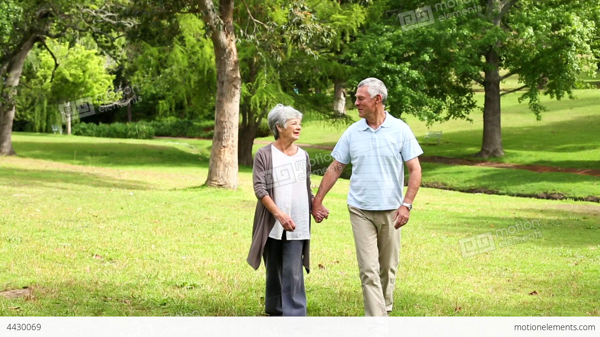 retired couple walking in the park together stock video