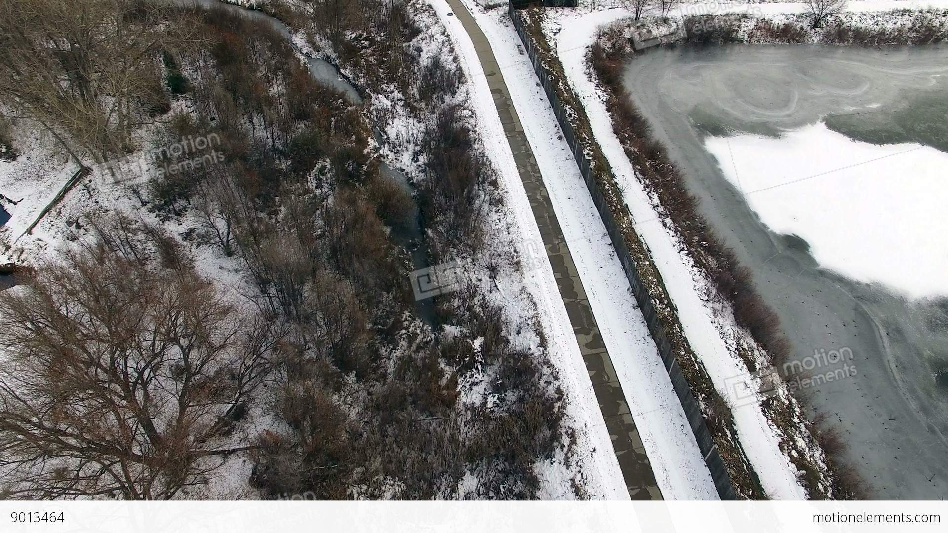 aerial drone tilt up snowy winter running path to frozen pond and