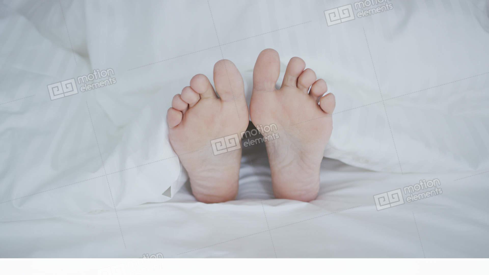 Crop Female Feet Under Blanket Stock Footage
