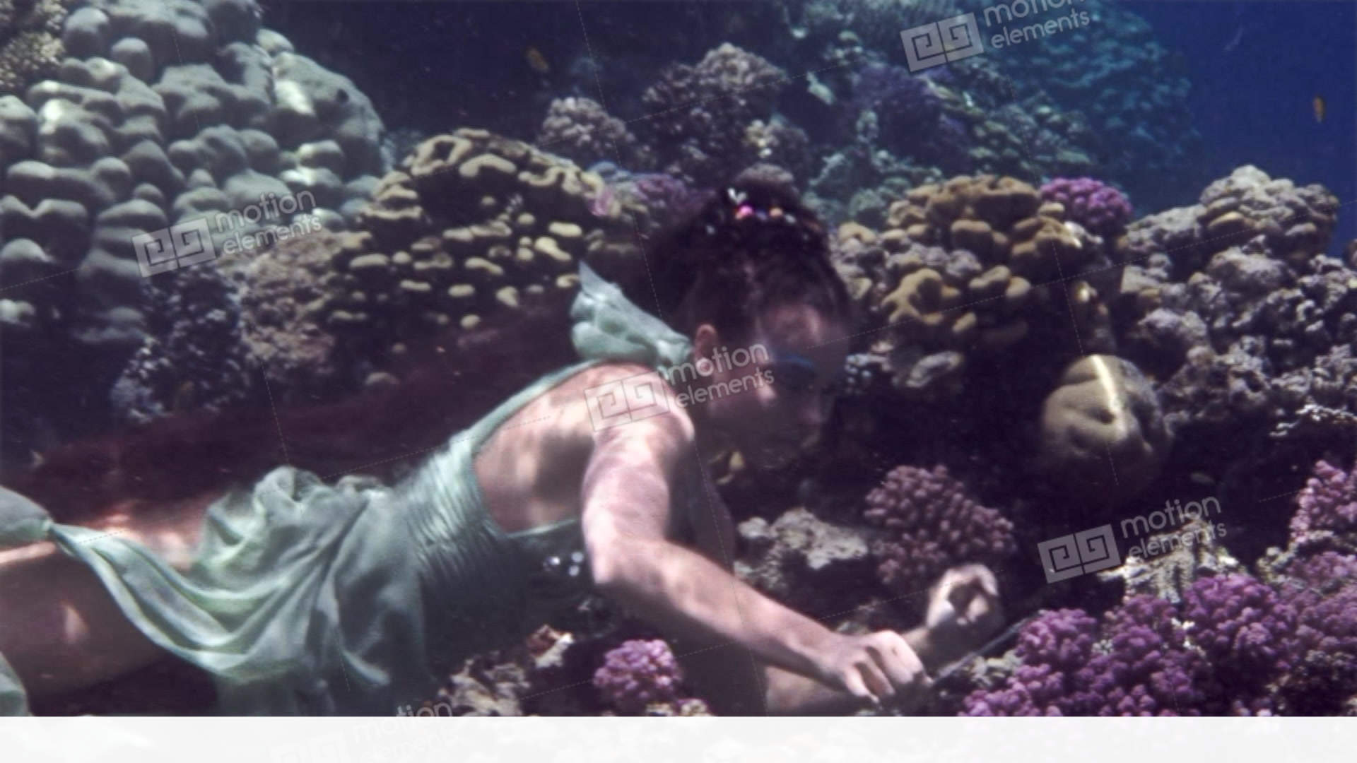Underwater model free diver poses for camera on background of corals