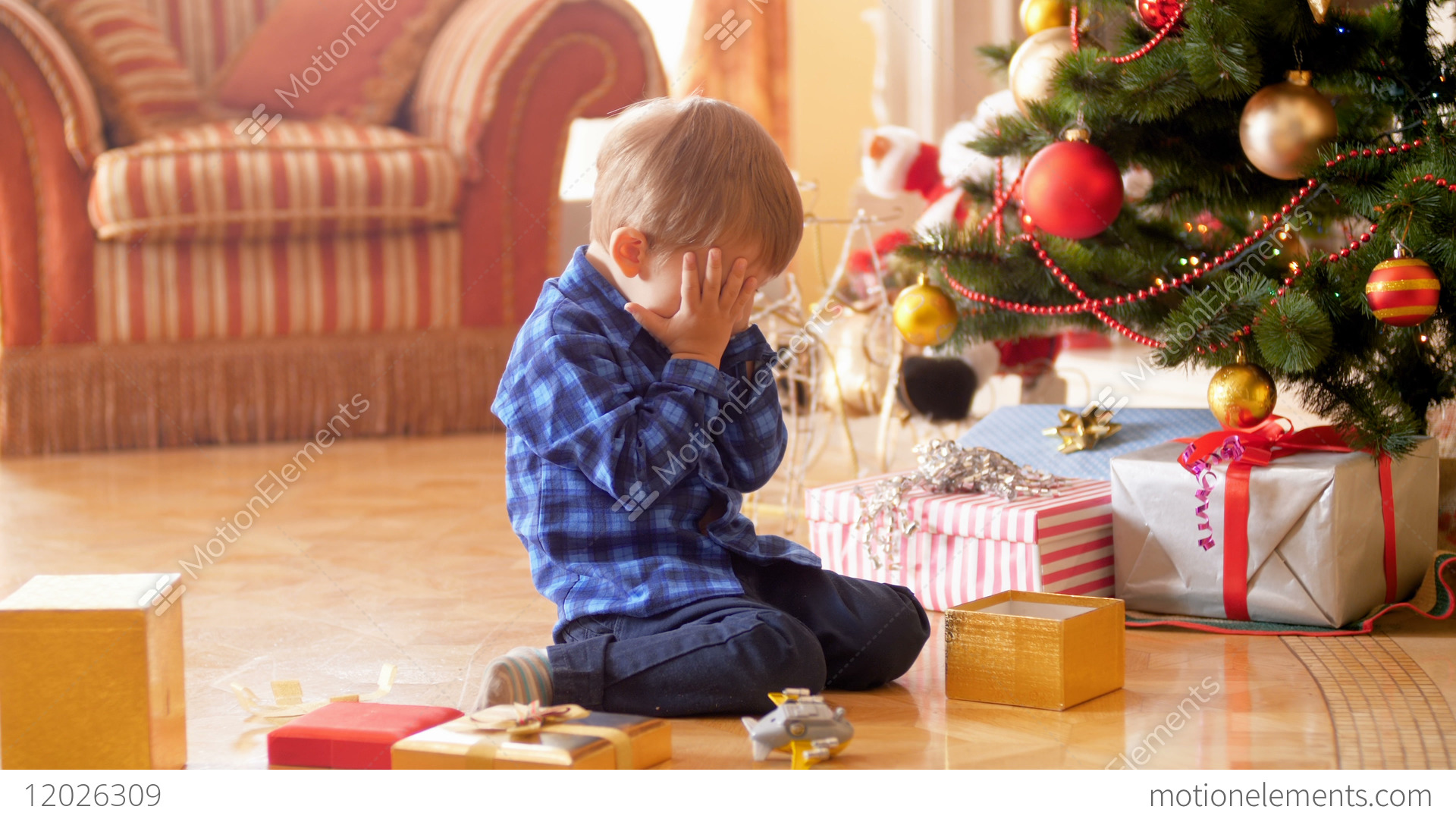 4k footage of upset little boy sitting under christmas stock video footage