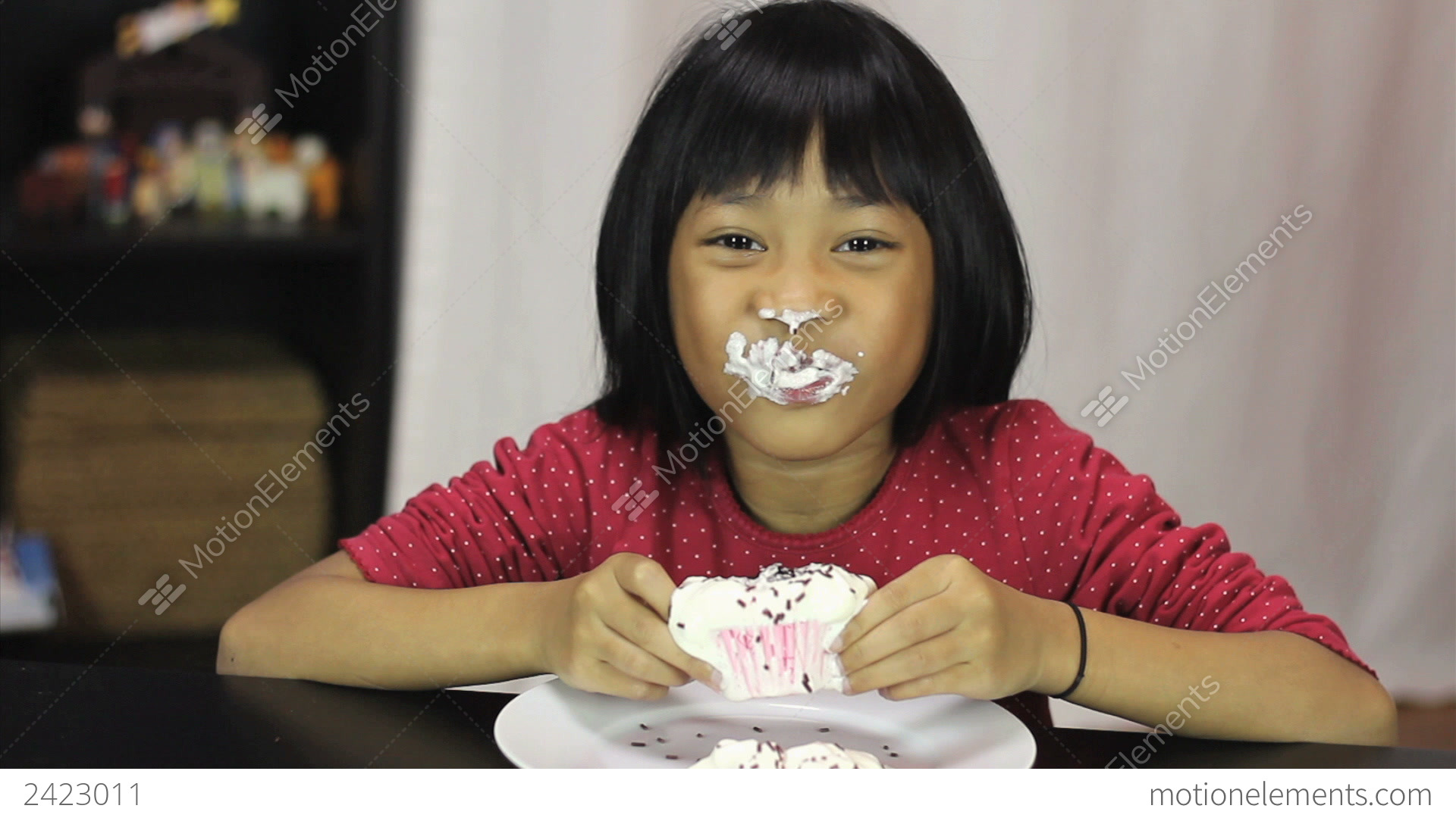 Little Asian Girl Eating Yummy Chocolate Cupcake Stock Video Footage