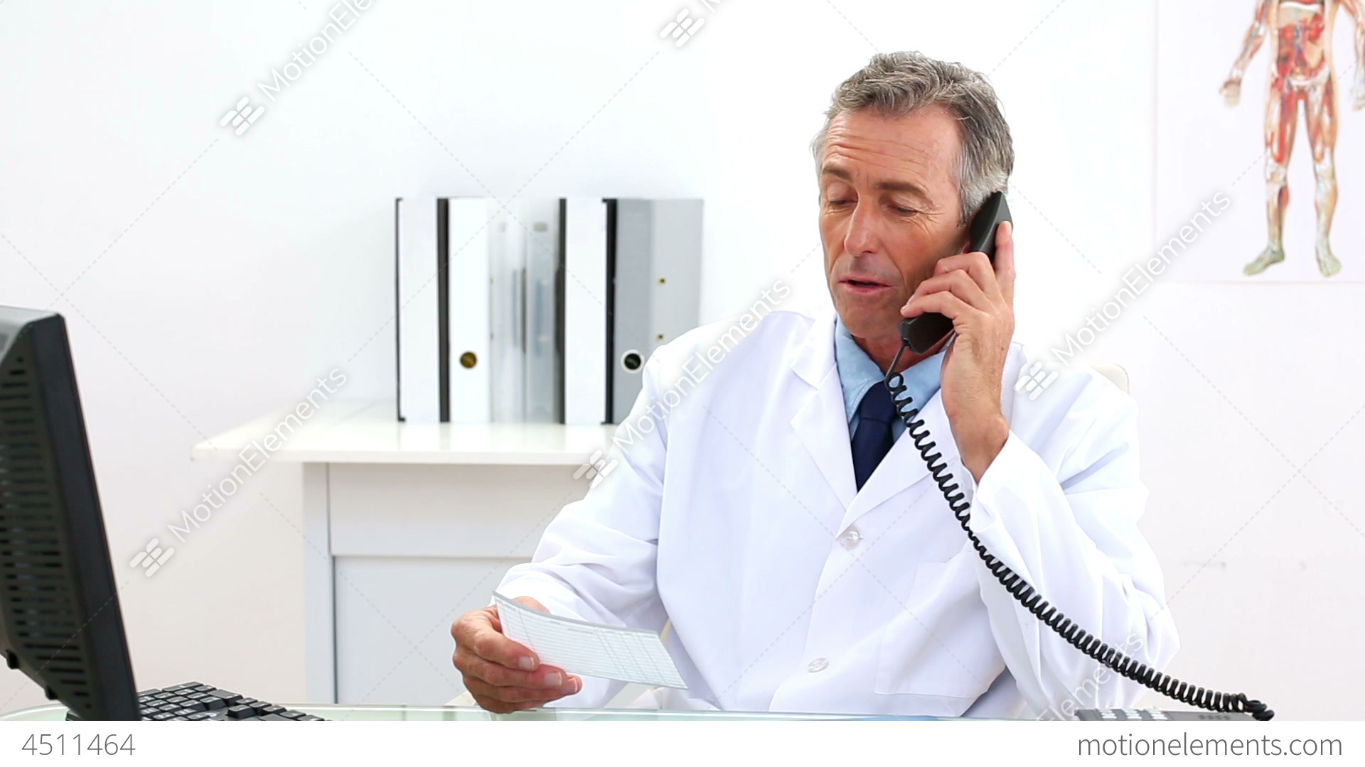 Mature Doctor Talking On The Phone At His Desk Stock Video