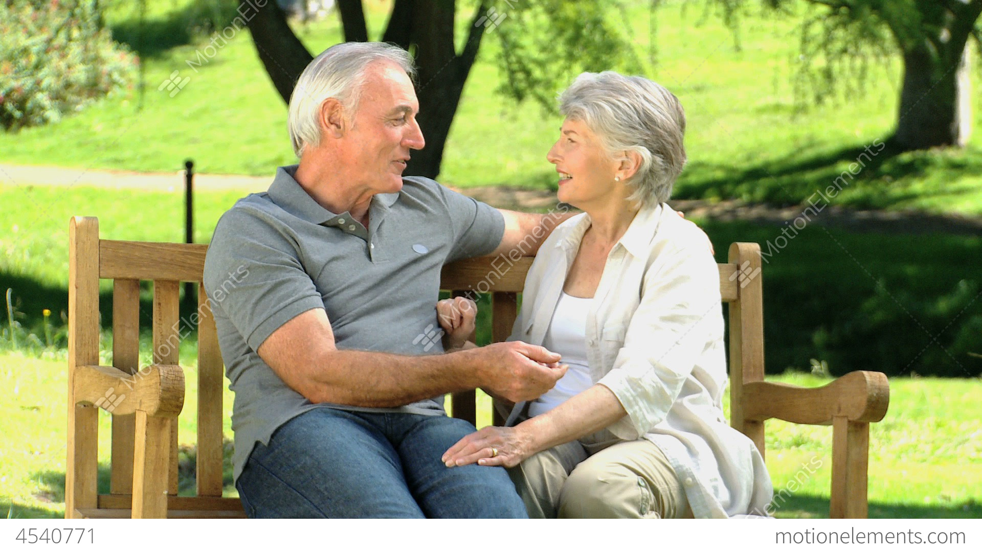 elderly couple sitting on a bench and talking stock video