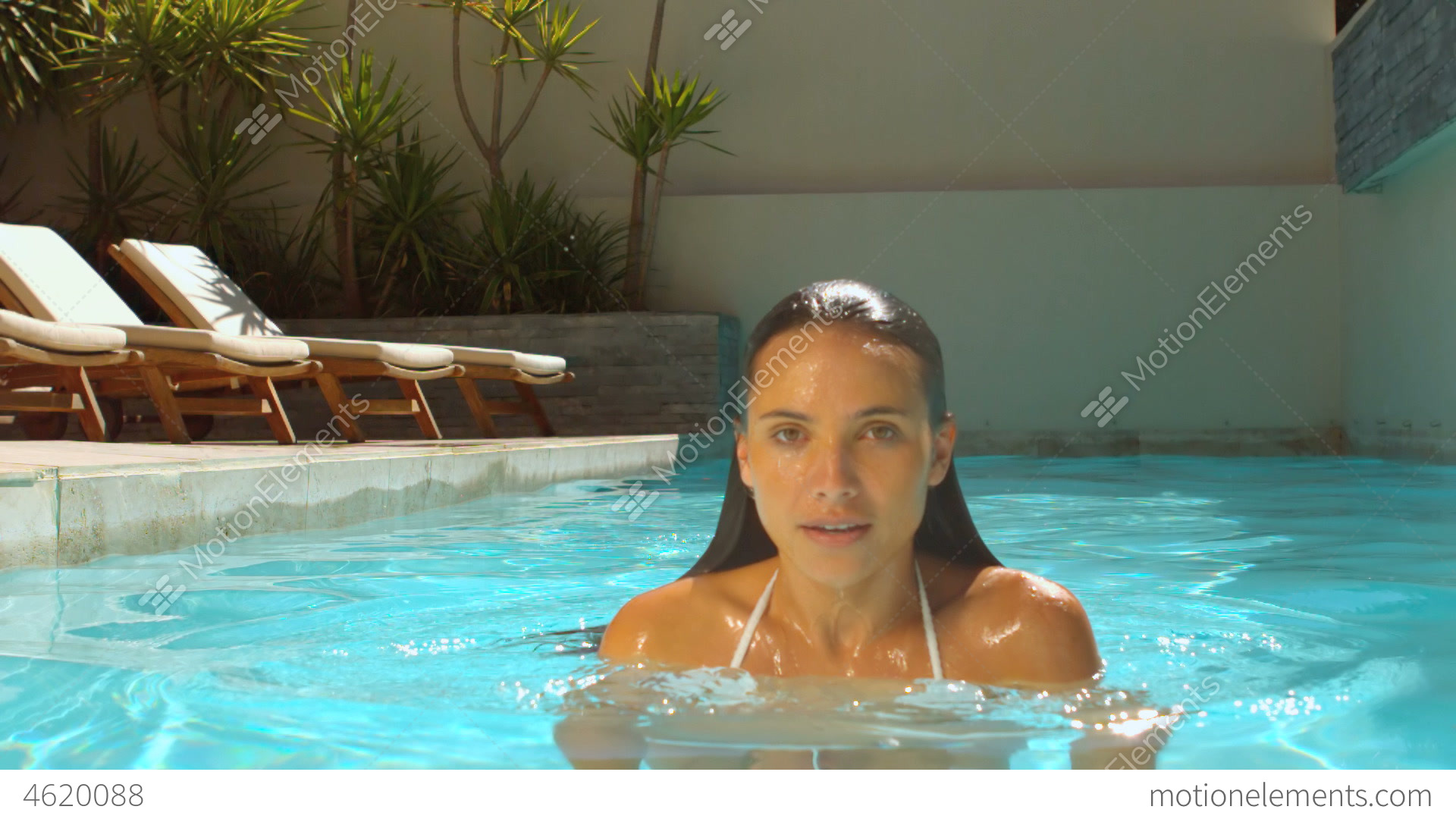 Woman emerging from swimming pool stock video footage Swimming pool beautiful