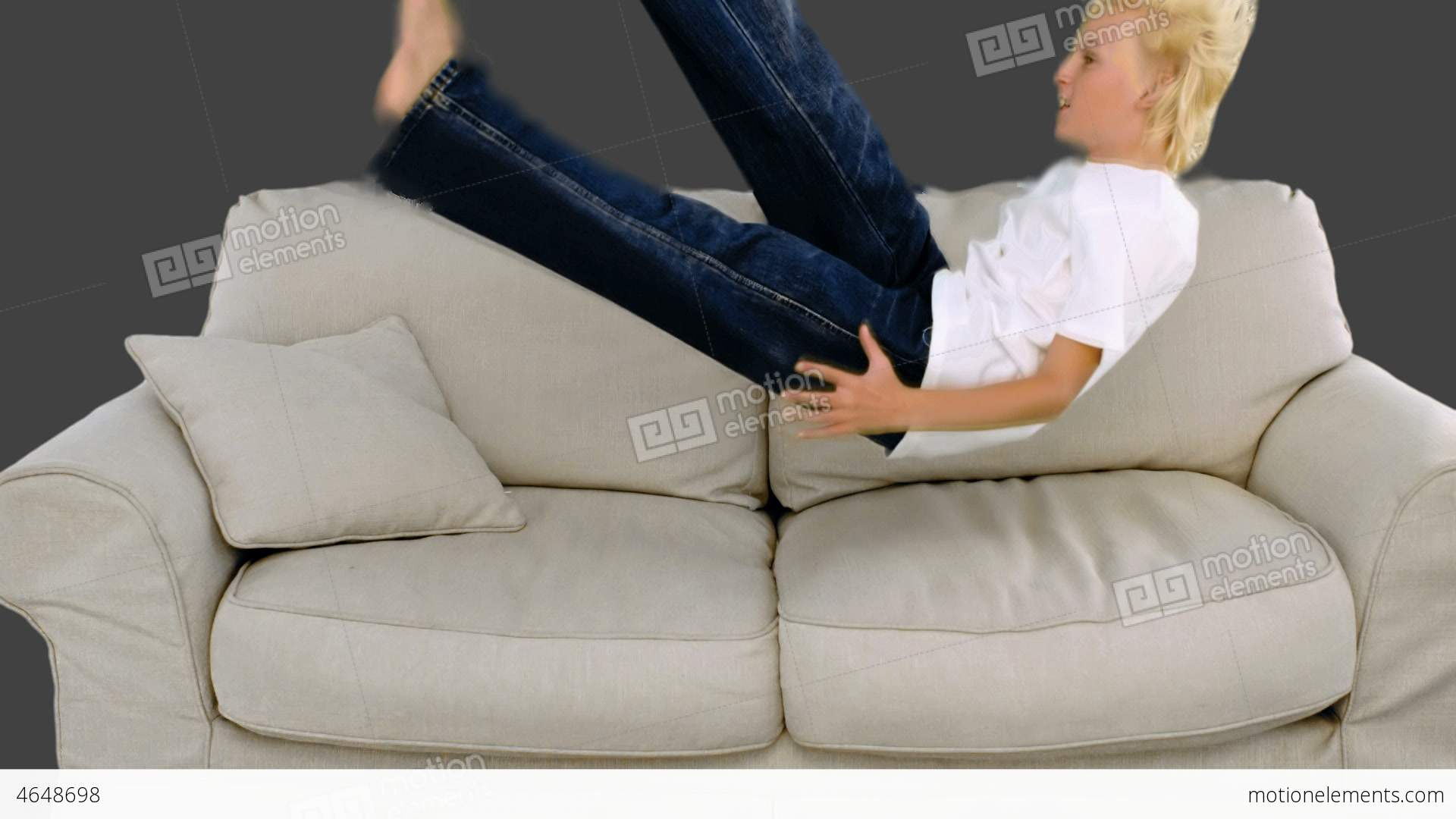 Young Boy Jumping On The Sofa On Grey Background Stock