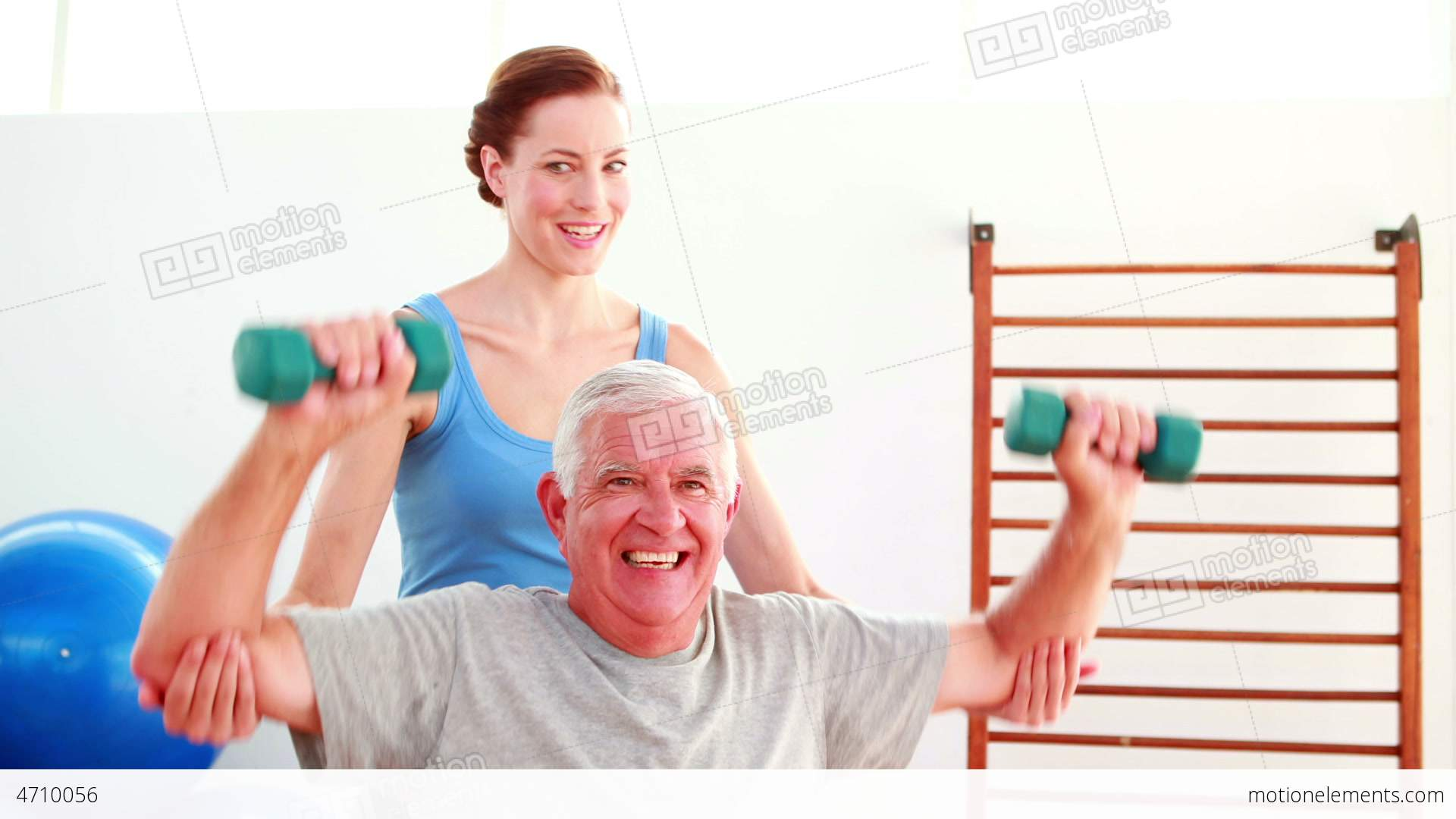 2fe542d58a9 Elderly man lifting hand weights sitting on exercise ball... Stock Video  Footage