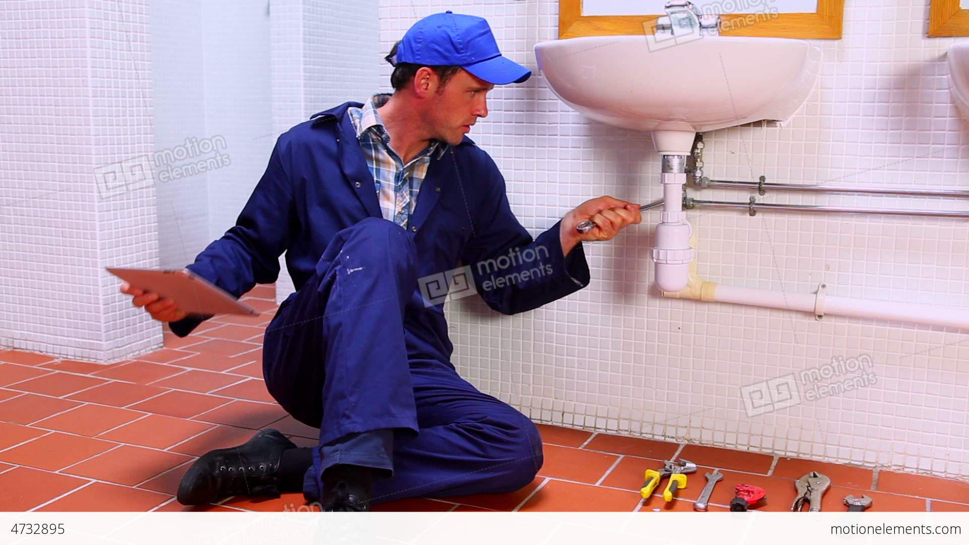 Handsome Plumber Fixing Sink And Checking Tablet P Stock video ...