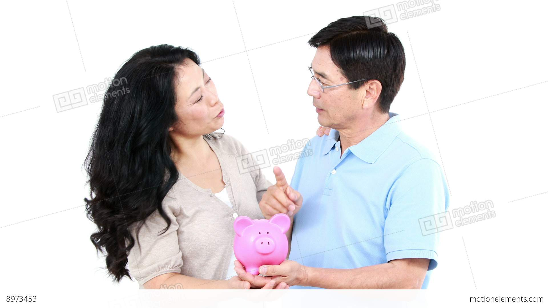 mature asian couple holding a piggy bank stock video footage | 8973453
