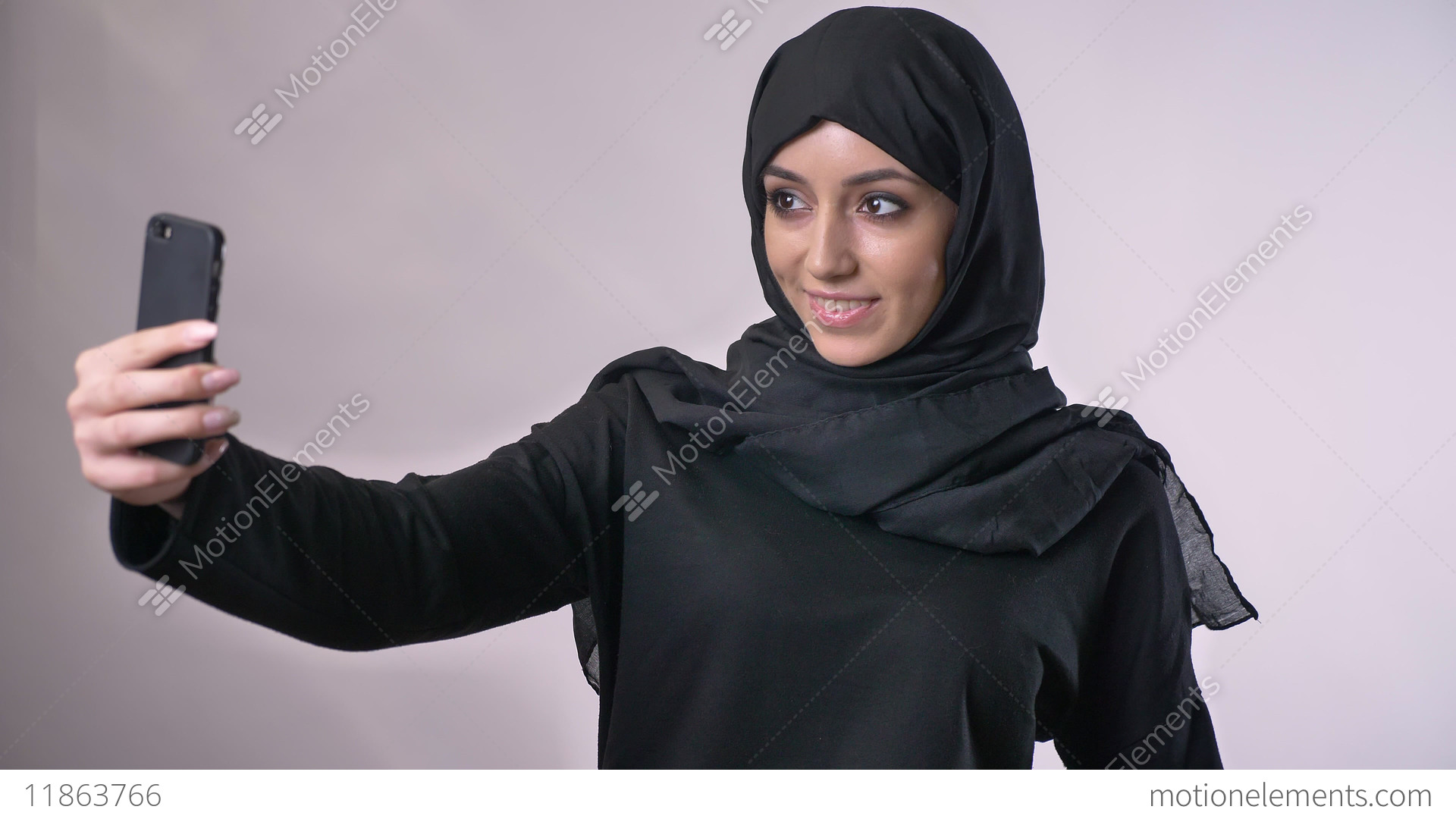 Young Beautiful Muslim Girl In Hijab Has A Video Call On Smartphone