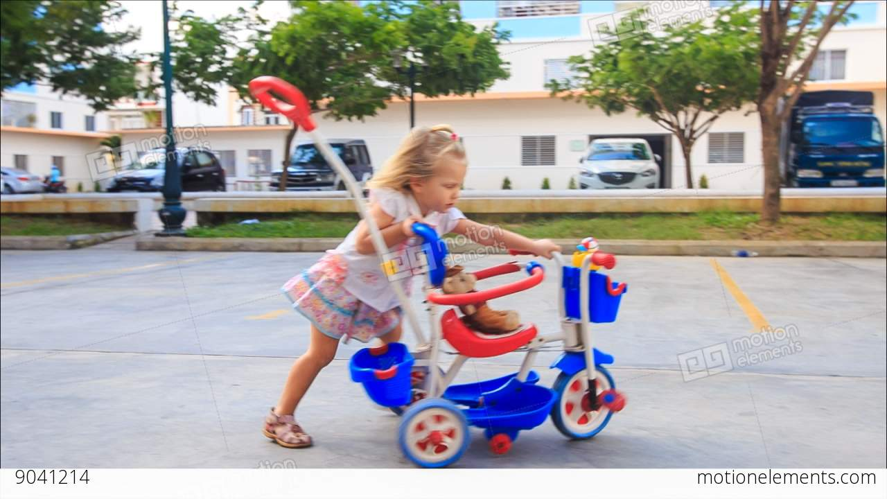 610838b1ff0 Little Blond Girl Pushes Pram Tricycle about Play Ground Stock Video Footage