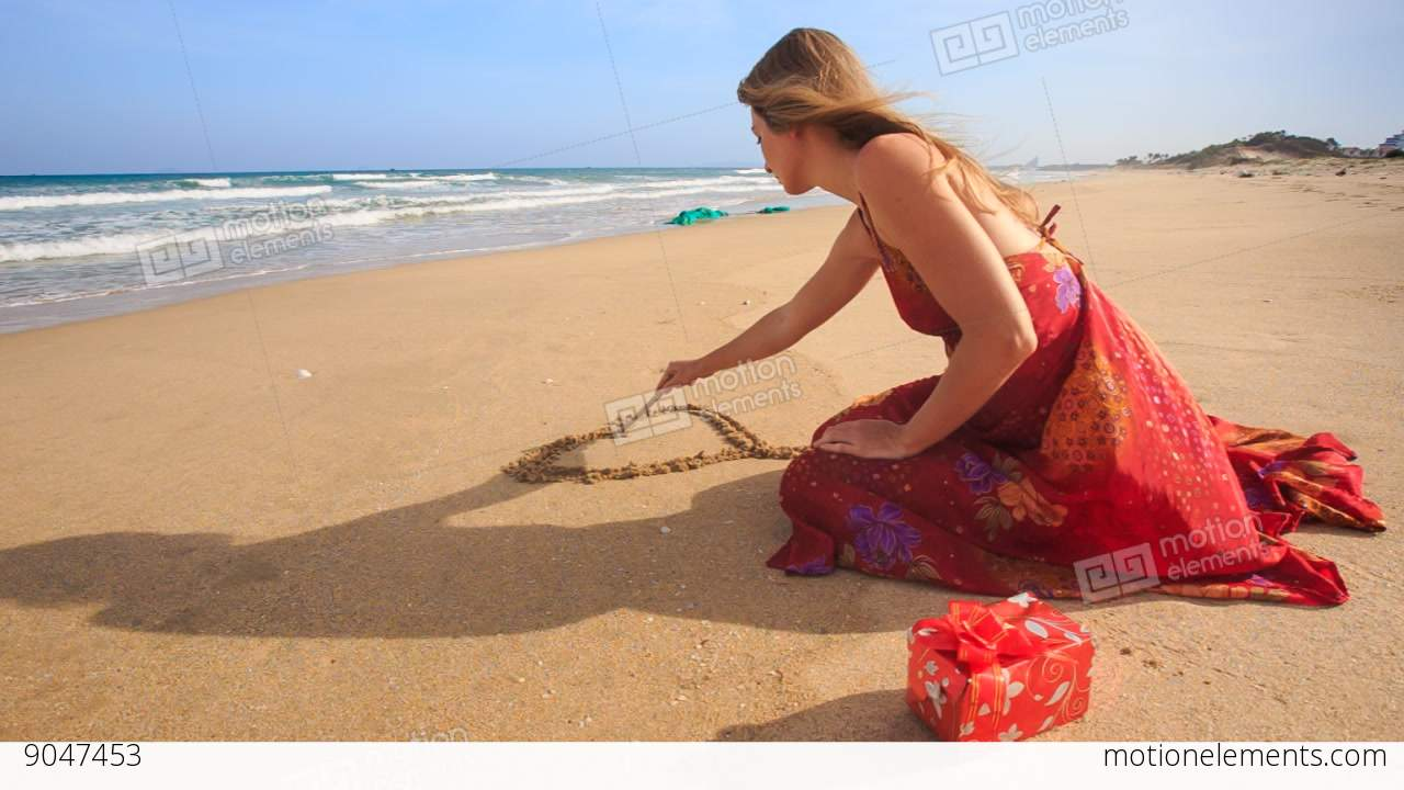 Woman In Red Dress Sits Draws Heart On Sand Of Wet Beach Stock Video Footage