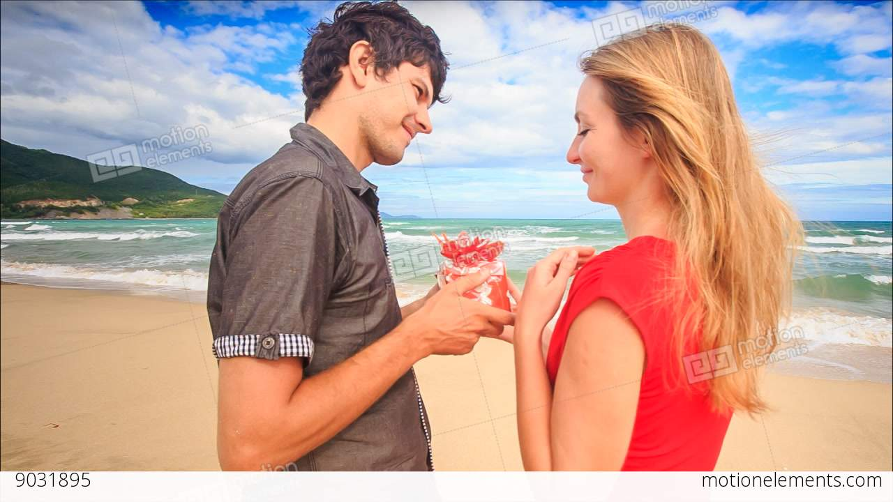 Guy gives gift to blond girl in red kiss hug on beach stock video guy gives gift to blond girl in red kiss hug on beach stock video footage thecheapjerseys Image collections